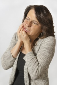 A woman suffering from TMD jaw pain.