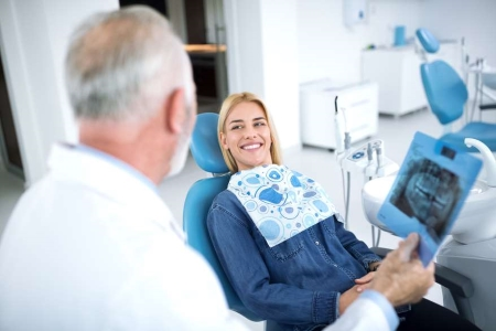 Happy female dental patient after oral surgery