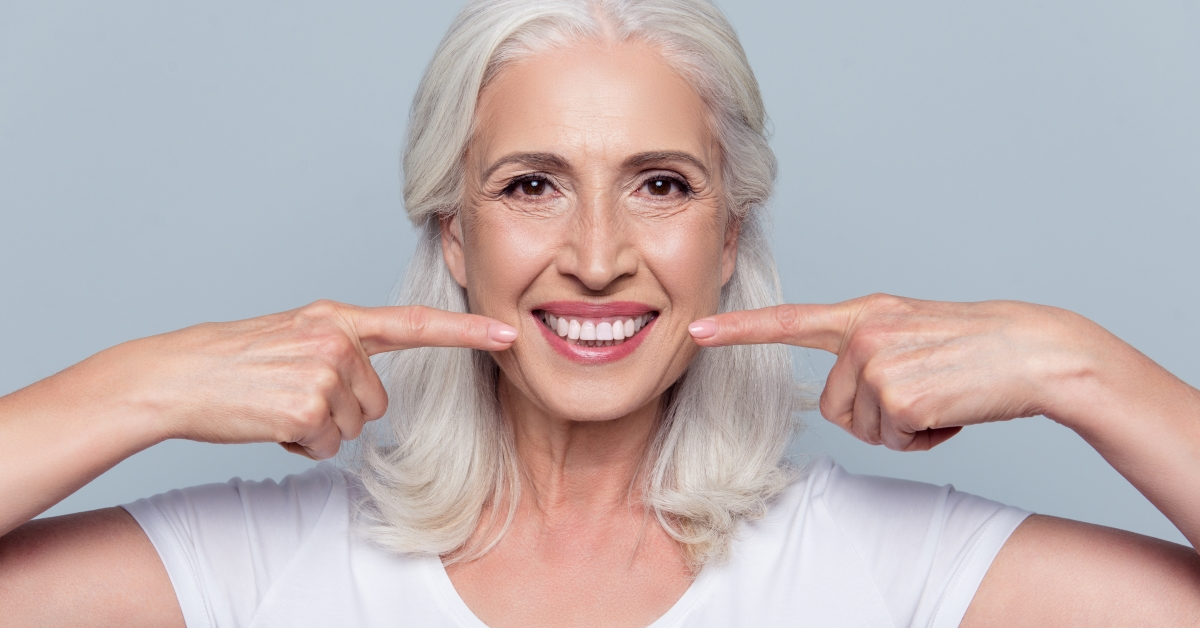 Teeth-in-a-day dental implants woman points to teeth
