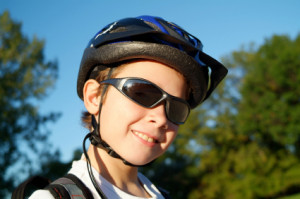 A boy with a helmet on his head; and wearing sunglasses while playing in the sun on his bike.